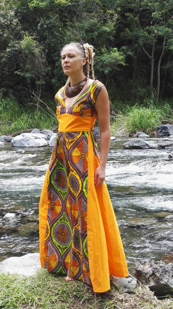 Robe longue en wax ton orange avec un coton orange uni, avec un collier en calebasse