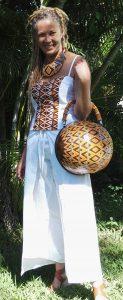 Mannequin avec un top moitié uni blanc et wax ton marron avec un pantalon large en coton blanc et un sac et collier en calebasse.